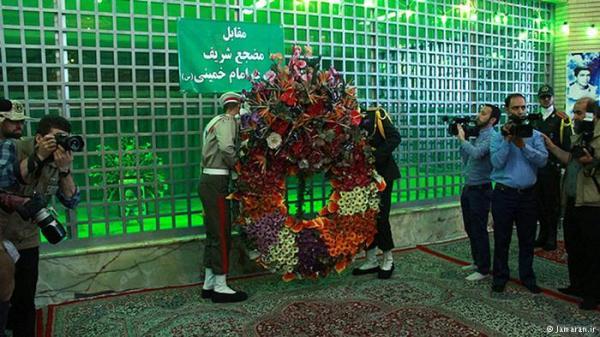 Anggota militer sedang meletakkan bunga di depan kuburan